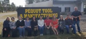 Pequot Tool staff standing and sitting in front of the Pequot Tool sign