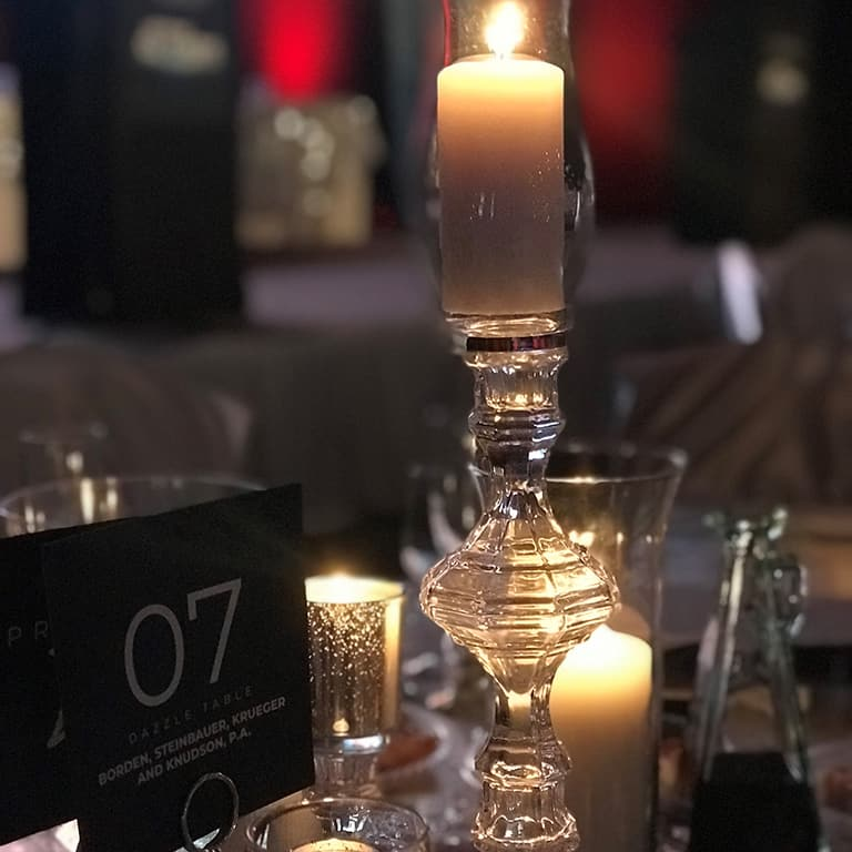 2021 Celebration Of Excellence photo of table decorations with stage in background 768x768
